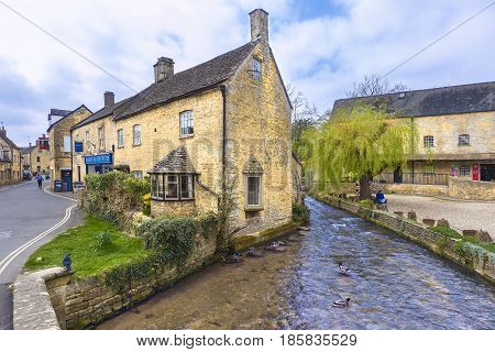 Bourton On The Water England - 7 April 2017 - Old stone buildings stand along a river at Bourton On The Water England on April 7th 2017.