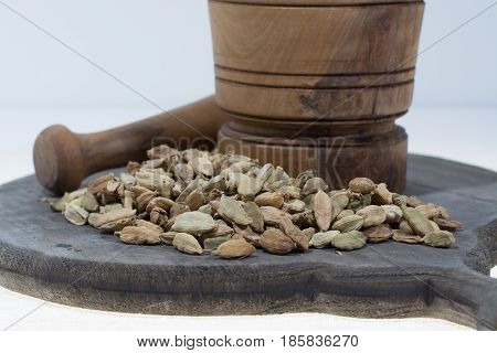 Raw Organic Cardamom Pods Ready to Use with mortar made from olive wood on white copy space