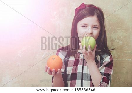 Adorable Girl Eating Green Apple With Orange In Hand
