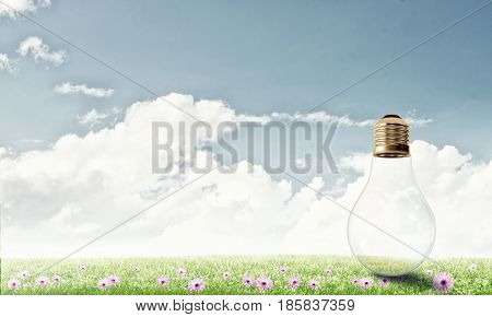 Electric light bulb against summer cloudy sky
