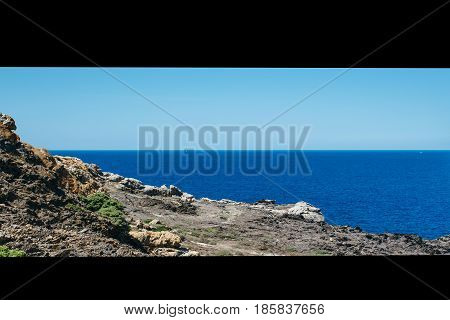 Horizontal outdoors shot of shoreline with rocks and calm blue sea.