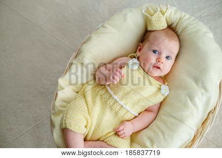 Portrait of newborn baby girl lying in a basket with golden crown and yellow bodysuit