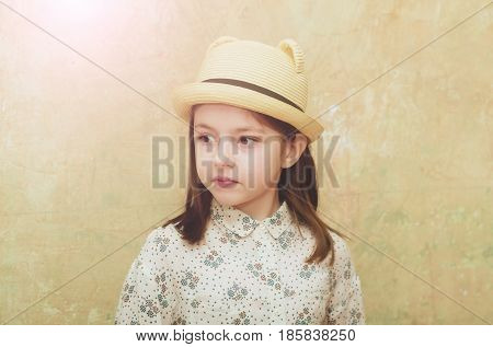 portrait of small little girl with brunette hair in fashionable retro hat on beige background. Childhood and happiness beauty and fashion vintage style