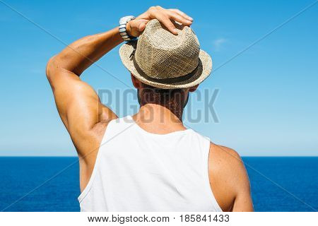 Back view of man at blue ocean admiring the seascape and holding his hat.