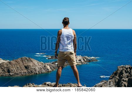 Back view of a muscular man admiring calm blue seascape from rocky shore.
