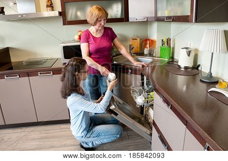 Girl And Woman Put Dishes In The Dishwasher