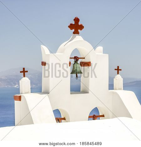 view of bell tower in Oia Santorini and part of caldera
