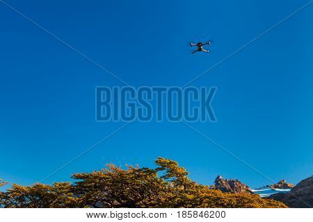 Dron with camera on blue sky background.