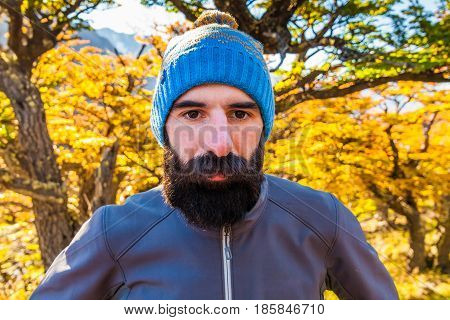 Bearded tourist man in the background of a autumn forest.