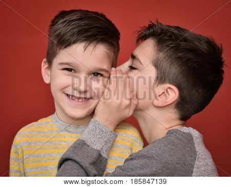 Young boy whispering secret into ears of smiling brother