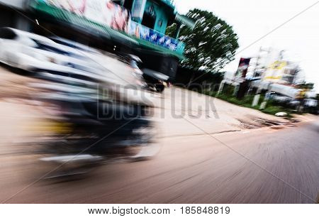 The motorcycle rides on the road at a fast speed. Motion blur.
