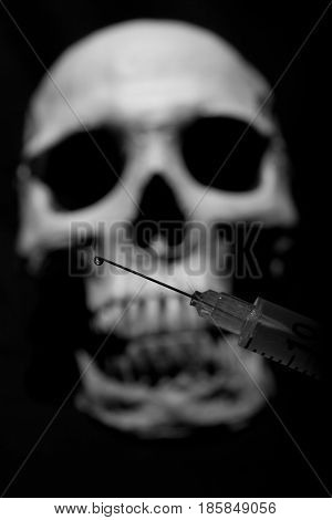 A drop of a drug on the tip of a syringe against the background of a human skull. Still life.
