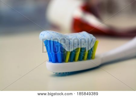 Toothbrush and toothpaste on blurred background lies empty tube of toothpaste