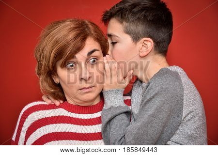 Young boy whispering secret into ears of surprised mother