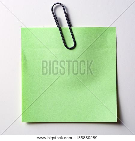 The green sticker with a gold paperclip isolated on white background.