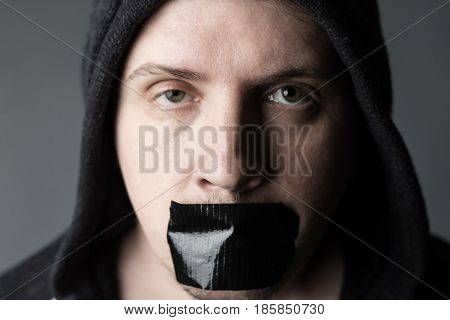 man with hood and covered mouth by black tape to forbidden him the free speeching in front of grey background