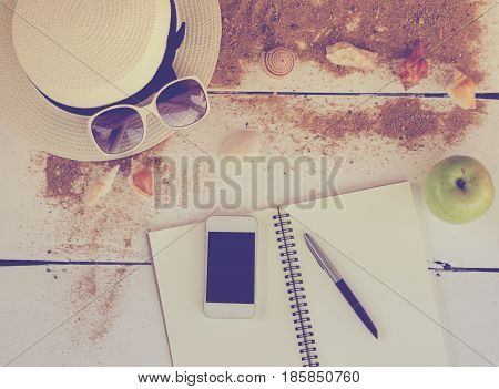 Travel accessories hats sun glasses notebook pen phone shell placed on a wooden floor