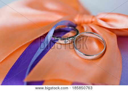 Wedding rings on a coral satin pillow. accessories wedding closeup. selective focus.