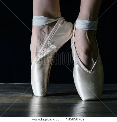 Close-up classic ballerina's legs in pointes on the black background and wooden grey floor