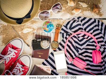 Travel accessories hats sunglasses notebook pen phone shell placed on a wooden floor