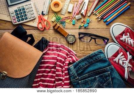 School supplies and costume placed on a wood background concept ready for school.