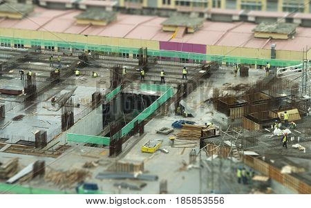 Miniature workers operating as a team on construction site