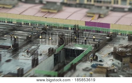 Miniature busy workers operating on construction site