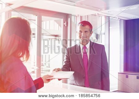 Businessman receiving document from receptionist in office