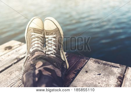 Man with crossed legs relaxing on wooden riverbank pier casual young guy wearing sneakers sitting by the river in summer afternoon selective focus