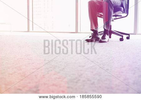 Low section of businessman sitting on office chair