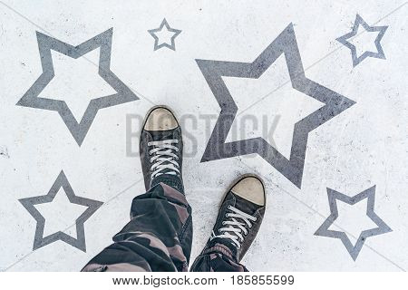 Sneakers on the road with star shape imprint - talent,   prize and award concept