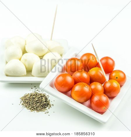cherry tomatos mozarella and ground basil with toothpicks on white background