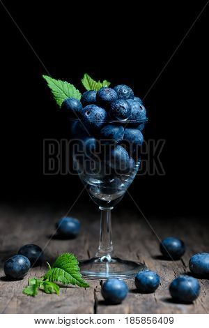 Blueberries with leaves in small glass, close up