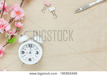 Top view business office desk background.The silver pen coffee beautiful pink flower wood white clock on wooden table backgtound with copy space.