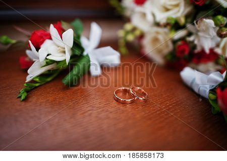 Wedding Rings With Bouquet And Buttonhole On Wooden Background.