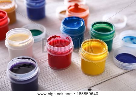 Color gouache jars closeup on white wood background. Artist workplace