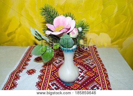 Flowers and twigs of pine stand in a vase on a napkin