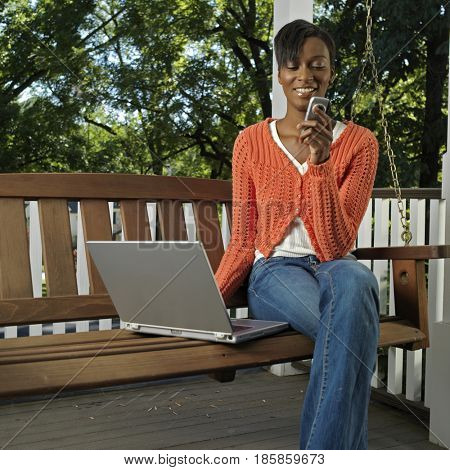 Mixed race woman on porch with cell phone and laptop