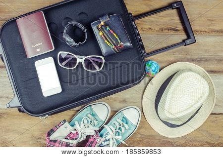Clothing traveler's Passport wallet glasses watches smart phone devices hat shoes on a wooden floor on the luggage ready to travel.