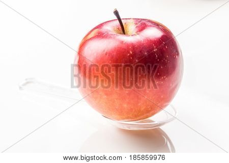 red apple on translucent medicine spoon on the table symbolising that drinking and eating of apple products prevents diseases and is full of vitamins