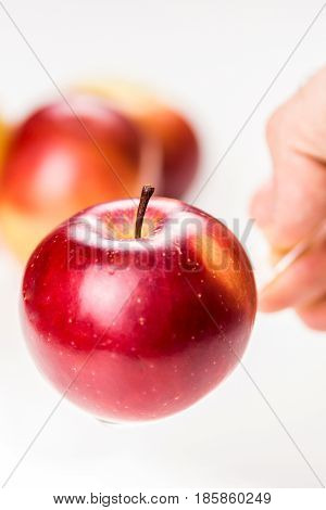 hand is holding red apple on translucent medicine spoon on the table symbolising that drinking and eating of apple products prevents diseases and is full of vitamins other apples at background