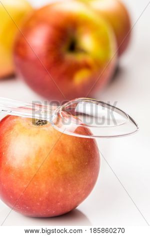 red apple and translucent medicine spoon on the table symbolising that drinking and eating of apple products prevents diseases and is full of vitamins other apples at background