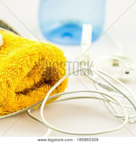 headphones mp3 player and orange towel symbols of modern lifestyle sport fitness activities measuring tape symbolising loosing weight when jogging regurarly