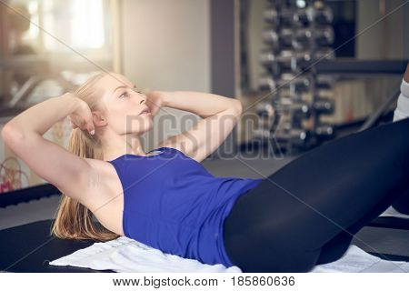 Pair of young adult women doing abdominal muscle Russian twist exercises while holding weights
