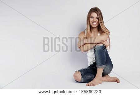 Beauty portrait of young attractive woman with straight long hair and barefoot posing in studio with copy space on background.