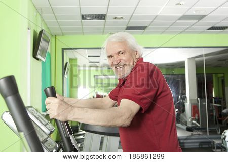 Senior man uses elliptical cross trainer in gym