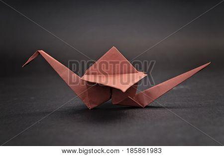 Orange crane or bird origami with black background