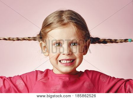 Funny picture of happy eyed girl with pigtails over pink background.