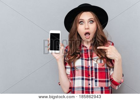 Portrait of a shocked casual girl in plaid shirt pointing finger at blank screen mobile phone isolated over gray background