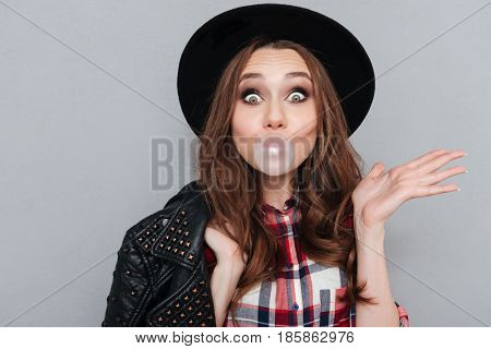 Close up portrait of a cute funny girl in hat chewing bubble gum and looking at camera isolated over gray background